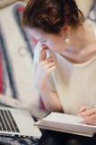 Denkendes Mädchen, das mit Laptop arbeitet Stockfoto