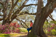 Denkendes Mädchen im schönen Park mit blühenden Blumen lizenzfreie stockfotos