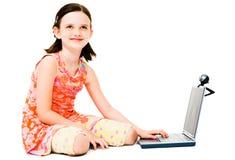 Denkendes Mädchen, das einen Laptop verwendet Stockfotografie