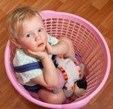 Denkendes nettes kleines Mädchen, das im Korb sitzt lizenzfreie stockbilder