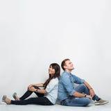Denkendes oben schauen der Mischrassepaare und Sitzen auf dem Boden b stockfoto