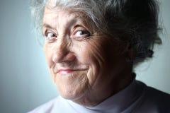 Denkendes Porträt der alten Frau auf Blau Stockfotografie