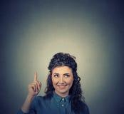 Denkendes Schauen der Frau oben, zeigend Finger auf leeren Kopienraum über Kopf Lizenzfreies Stockbild