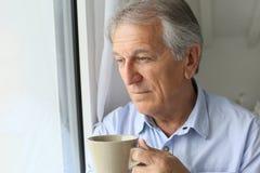 Denkendes Schauen des älteren Mannes durch das Fenster Stockfotos