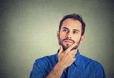 Denkendes träumendes Schauen des glücklichen Mannes oben lokalisiert auf grauem Wandhintergrund Lizenzfreie Stockfotos