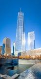 9/11 Denkmal am World Trade Center-Bodennullpunkt mit einem World Trade Center-Turm auf dem Hintergrund - New York, USA Stockbild