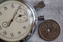 Denmark coin with a denomination of two crown (krone) (back side) and stopwatch on flax canvas backdrop - business background. Denmark coin with a denomination stock image