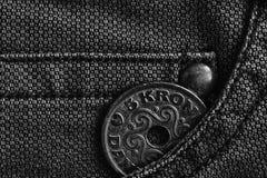 Denmark coin denomination is 5 krone crown in the pocket of worn denim jeans, monochrome shot. Denmark coin denomination is five krone crown in the pocket of Stock Images