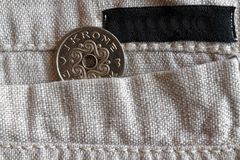 Denmark coin denomination is 1 krone crown in the pocket of old linen pants with black stripe. Denmark coin denomination is one krone crown in the pocket of old Royalty Free Stock Photography
