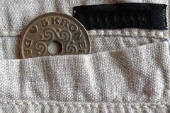 Denmark coin denomination is 5 krone crown in the pocket of old linen pants with black stripe. Denmark coin denomination is five krone crown in the pocket of old Stock Photography