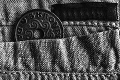 Denmark coin denomination is 5 krone crown in the pocket of old linen pants with black stripe, monochrome shot. Denmark coin denomination is five krone crown in Stock Images