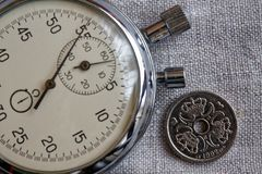 Denmark coin with a denomination of one crown (krone) (back side) and stopwatch on flax canvas backdrop - business background. Denmark coin with a denomination stock images
