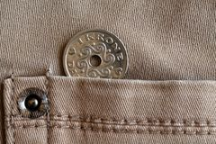 Denmark coin denomination is one krone crown in the pocket of beige denim jeans.  Royalty Free Stock Photo