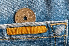 Denmark coin denomination is one krone crown in the pocket of worn blue denim jeans with yellow stripe. Denmark coin denomination is 1 krone crown in the pocket Stock Image