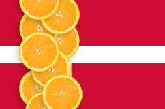 Denmark flag and citrus fruit slices vertical row. Denmark flag and vertical row of orange citrus fruit slices. Concept of growing as well as import and export royalty free stock photography