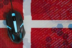 Denmark flag and computer mouse. Digital threat, illegal actions on the Internet. Denmark flag and modern backlit computer mouse. The concept of digital threat stock image