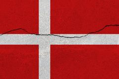 Denmark flag on concrete wall with crack. Patriotic grunge background. National flag of Denmark stock photo
