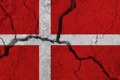Denmark flag on the cracked earth. National flag of Denmark. Earthquake or drought concept royalty free stock image