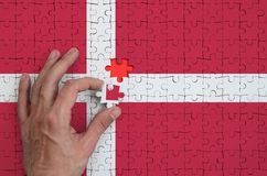 Denmark flag is depicted on a puzzle, which the man`s hand completes to fold.  stock images