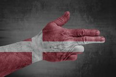 Denmark flag painted on male hand like a gun. On concrete background royalty free stock images