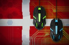 Denmark flag and two mice with backlight. Online cooperative games. Cyber sport team. Denmark flag and two modern computer mice with backlight. The concept of stock images