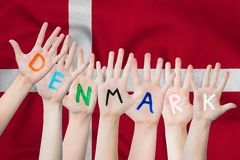 Denmark inscription on the children`s hands against the background of a waving flag of the Denmark.  royalty free stock photos
