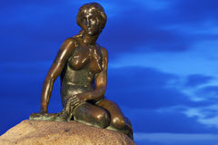 Denmark: Little Mermaid. Statue of Little Mermaid familiar from H. C. Andersen's fairytales in Copenhagen in the evening with a blue sky stock images