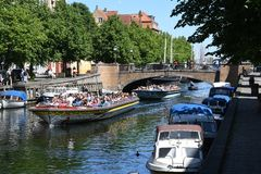 DENMARK`S WEATHER_SUN SHINE BOAT CRUSING TOURISTS. Copenhagen/Denmark 25.May 2018_ Foreign and local tourists enjoy boat canal crusing in Christianshavn canal in Royalty Free Stock Images