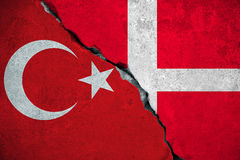 Denmark vs turkey, red turkey flag on broken damage brick wall and half denmark flag background, relationship crisis politics war Royalty Free Stock Image