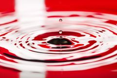 Denmark Water drip close macro flag of country. Denmark Water dripping or water ripples in a pond. waves of rippling flag of country royalty free stock photo