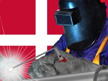 DENMARK WELDER WITH BACKGROUND OF HIS FLAG WAVES. WORKER THAT GENERATES WELL-BEING AND RICHES TO HIS COUNTRY AND TO THE WHOLE WORLD Stock Photography