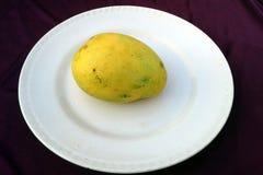 Denna är bilden av gula frukter för en mango som sätts i en platta royaltyfri bild