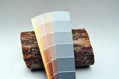 Denna är en cederträjournal med flera målarfärgchiper som lutar på den för jämförelse Arkivfoton