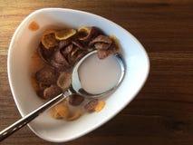 Denna är frukostcornflakes i en vit bunke Förlagt på ett trä Royaltyfri Foto