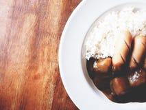 Denna är kareraisucurry över ris i den vita plattan ovanför trä Arkivfoto