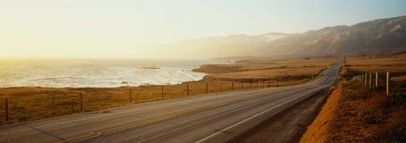 Denna är routen 1also som vets som Stillahavskustenhuvudvägen Vägen placeras bredvid hav med bergen i avståndet Fotografering för Bildbyråer