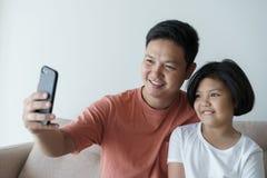 Denna asiatiska familj har en fader och en dotter Lite den videopd appellen för flickan och för fadern är de lyckliga i deras hem fotografering för bildbyråer