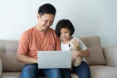Denna asiatiska familj har en fader och en dotter Lite ser flickan och fadern bärbara datorn som de är lyckliga i deras hem royaltyfri fotografi