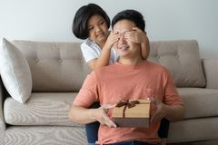 Denna asiatiska familj har fadern och dottern Lite flickan som framlägger en födelsedaggåvaask för att avla är de, lyckliga i der royaltyfria foton
