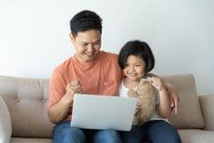 Denna asiatiska familj har fadern och dottern Lite ser flickan och fadern bärbara datorn som de är lyckliga i deras hem royaltyfria bilder
