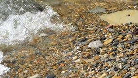 Denna fala obmyć otoczaka plaża przy zmierzchem zbiory