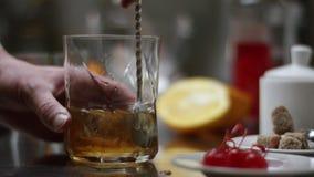 Denna klassiska bourboncoctail H?llande whisky f?r bartender i exponeringsglaset med iskuber p? tr?tabellen och svart m?rker arkivfilmer