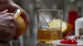 Denna klassiska bourboncoctail tar en festlig v?nd med en f?rgst?nk av orange fruktsaft h?llande whisky f?r bartender i exponerin lager videofilmer