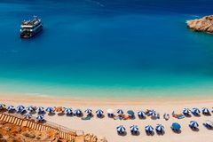 Denna piasek plaża z turystami sunbathing pod parasolami i podróży łodzią w wodzie obrazy stock