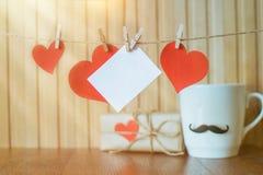 Denna ?r mappen av formatet EPS10 Kort för meddelande med pappers- hjärtor som hänger med klädnypor över träbräde F?delsedag red  arkivbild