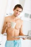 dennakna manlign med kuper av tea läser tidningen royaltyfri bild