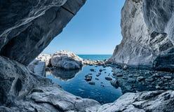 Denne jam skały Grota z wodnymi odbiciami Zdjęcie Royalty Free