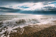 Denne ocean fala Myje otoczaków kamieni plażę Przy Chmurnym lato wieczór Zdjęcie Stock