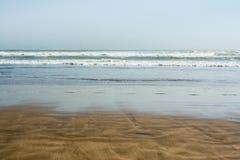 Denne pływowe fala z bielem pienią się na mokrej pogodnej piaskowatej plaży Fotografia Royalty Free