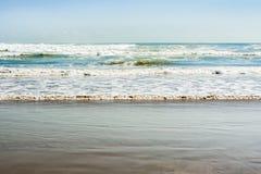 Denne pływowe fala z bielem pienią się na pogodnej piaskowatej plaży w kurorcie Obrazy Royalty Free